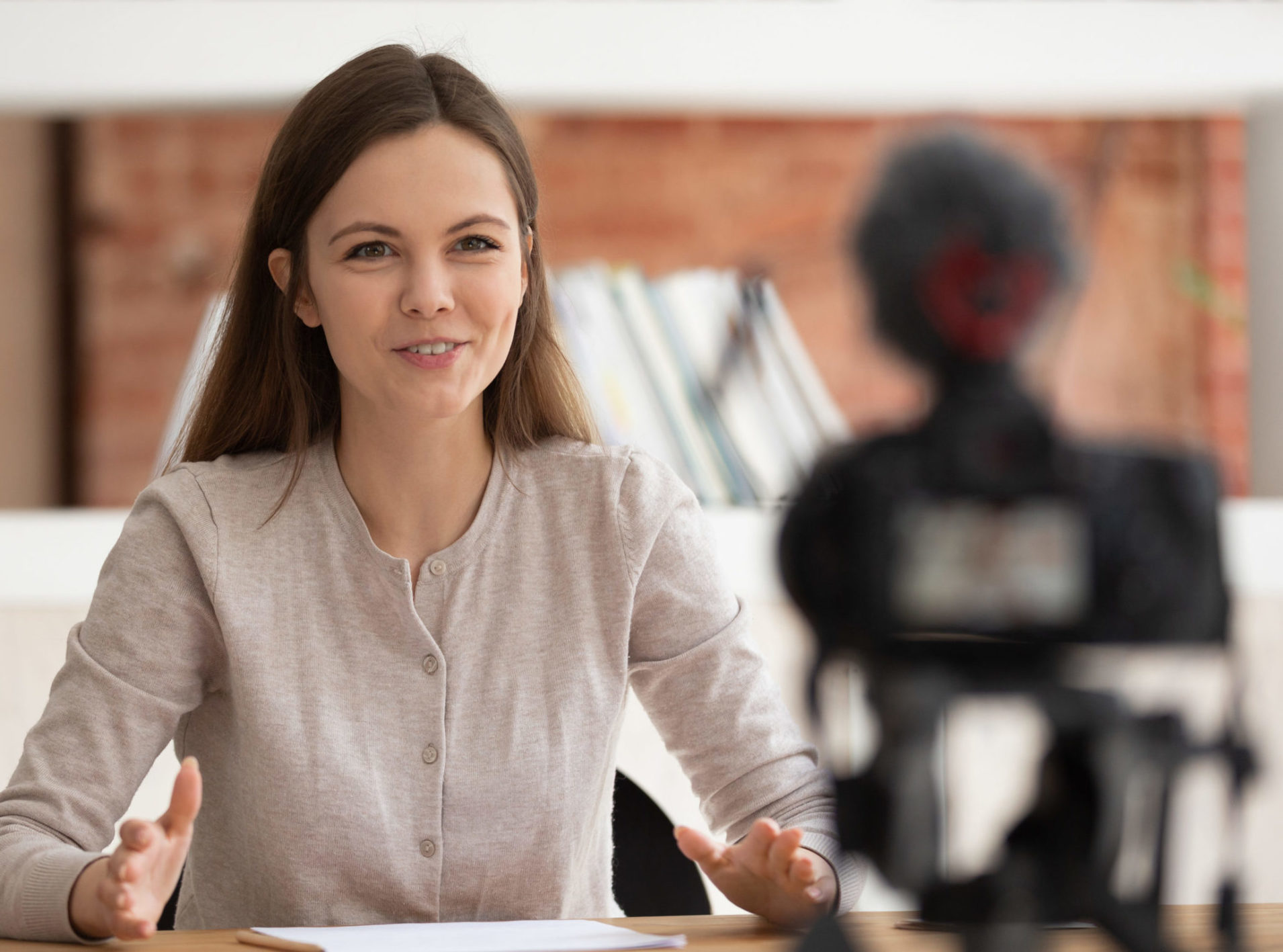 Smiling young female tutor or coach talk at professional camera shooting online training study course, positive motivated girl vlogger speak with viewers making video, record live vlog or tutorial